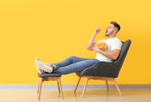 Handsome Young Man With Tasty Potato Chips Sitting In Armchair Near Color Wall