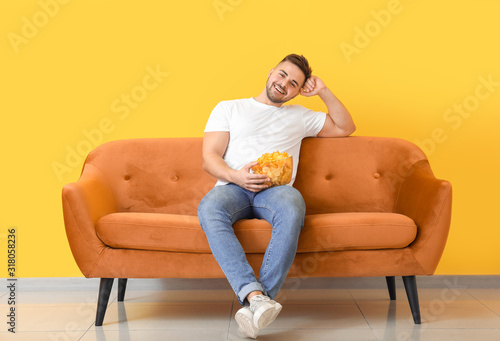 Cuadros en Lienzo Handsome young man with tasty potato chips sitting on sofa near color wall