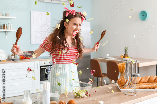 Foto Funny angry housewife cooking in kitchen