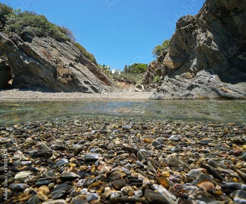 Mediterranean sea small cove on rocky shore with pebbles underwater, split view over and under water surface, Spain, Costa Brava, Cadaques, Catalonia, Cap de Creus, Cala Jonquet #318059428