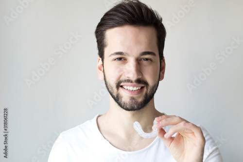 Close-up Of A Man's Hand Putting Transparent Aligner In Teeth Wallpaper Mural