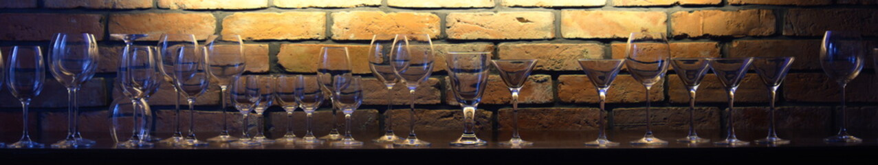 Glasses against the backdrop of an illuminated brick wall
