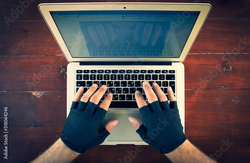 Cuadros en Lienzo look down to the males hands with gloves typing on laptop keyboard on the red wood background