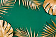 canvas print picture - Gold tropical palm leaves Monstera on green background. Flat lay, top view minimal concept.