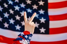 Cropped Image Of Hand Showing Peace Sign Against American Flag