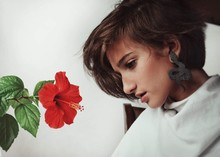 Side View Of Thoughtful Young Woman By Red Hibiscus At Home