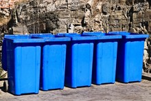 Closeup Shot Of A Lineup Of Blue Garbage Bins In Front Of A Rock Formation