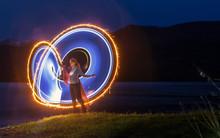 Woman Making Lighting Paintings By Lake At Night