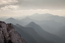 Beautiful, Soft, Endless, Pointy Mountain Layers In The Distance, Bright Sky And Mist With Foreground Rocky Cliff