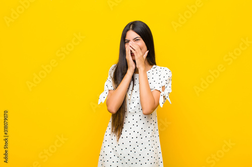 young pretty latin woman looking happy, cheerful, lucky and surprised covering m Canvas Print