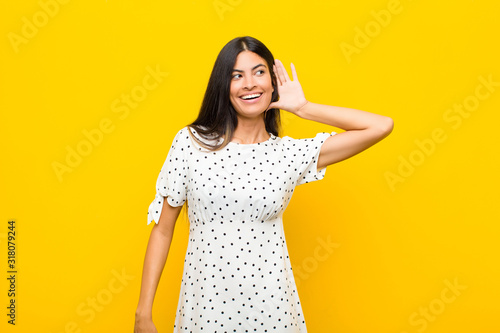 Photo young pretty latin woman smiling, looking curiously to the side, trying to liste