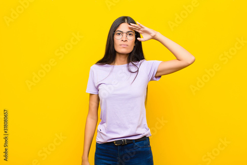 Fototapeta young pretty latin woman greeting the camera with a military salute in an act of honor and patriotism, showing respect against flat wall obraz