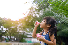 Girl Blowing Bubbles By Pond