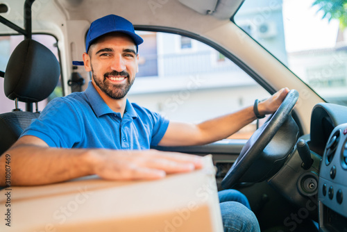 Fotografie, Obraz Delivery man driving van with cardboard boxes on seat.