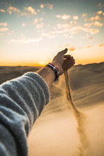 Cropped Hand Of Man Falling Sand On Desert Against Sky During Sunset