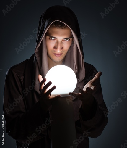 Fotografia Young wizard with crystal ball in dark room
