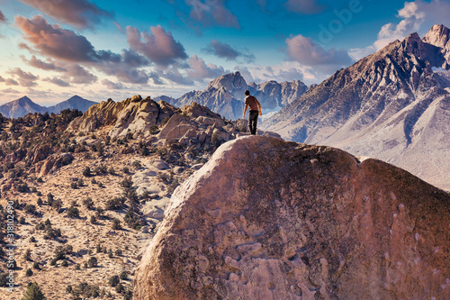 Man rock climbs on huge granite boulder in the Buttermilk area of Bishop, Califo Poster Mural XXL