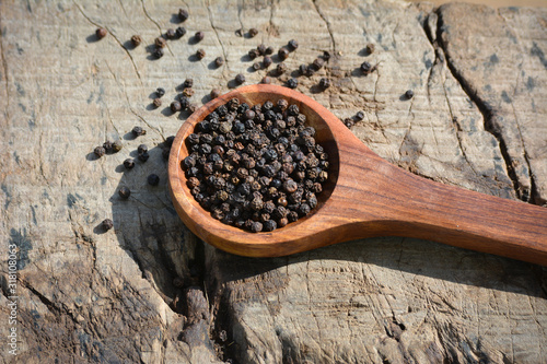 Black peppercorns in wooden spoon on wooden background Canvas Print