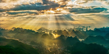 SUNLIGHT STREAMING THROUGH CLOUDS OVER LANDSCAPE