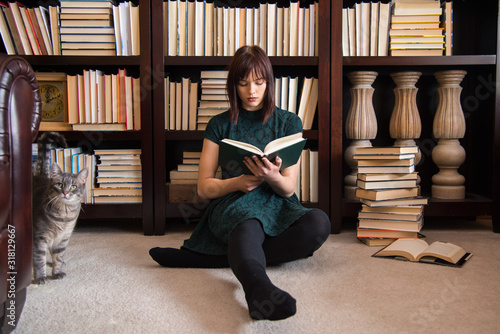 Carta da parati Young Woman Reading Book While Sitting Against Bookshelf In Library