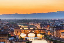 High Angle View Of Ponte Vecchio Over River Amidst Buildings Against Sky During Sunrise