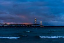 Mackinac Bridge Over Bay Of Water Against Cloudy Sky At Dusk