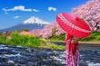 Leinwanddruck Bild - Asian woman wearing japanese traditional kimono and looking at cherry blossoms with fuji mountains in Shizuoka, Japan.