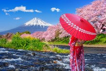 Asian Woman Wearing Japanese Traditional Kimono And Looking At Cherry Blossoms With Fuji Mountains In Shizuoka, Japan.