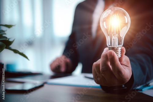 Photo businessman hand holding light bulb with finance document and tool,concept of New ideas for business and fonance