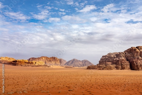 Cliffs and caves on a desert full of dry grass under a cloudy sky during daytime