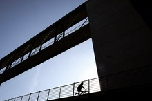 Low Angle View Of Silhouette Man Riding Bicycle On Footbridge Bridge