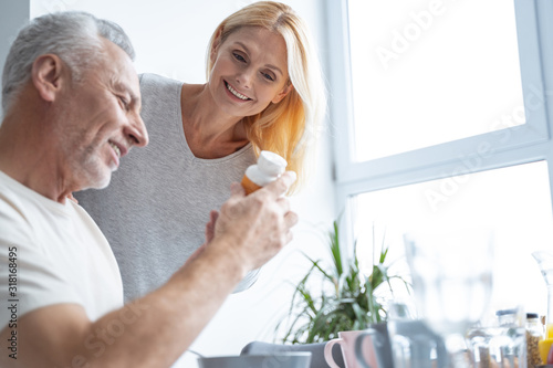 Fototapeta Happy woman and man looking at pills stock photo obraz
