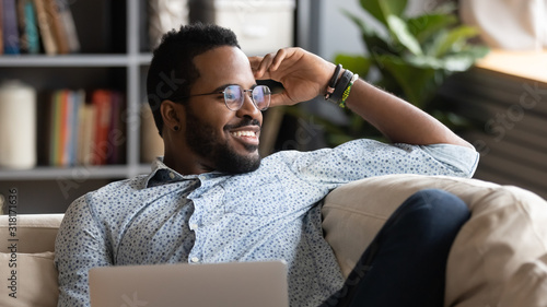 Fototapeta Happy african american man relaxing with laptop looking away dreaming obraz