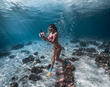 Full Length Of Woman Holding Camera In Sea