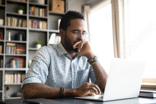 Focused concentrated african businessman sit at desk look at laptop