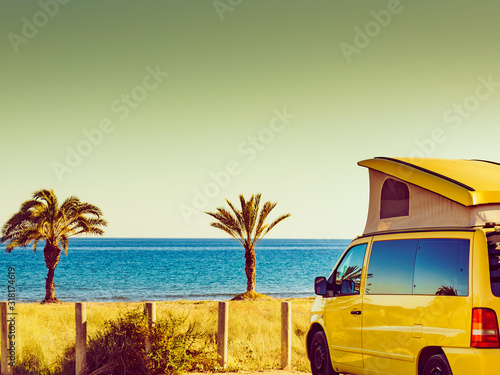 Fotografija Camper van with tent on roof on beach