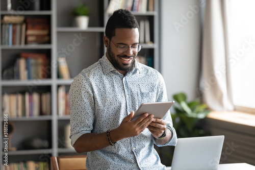 Smiling african business man using digital tablet computer in office
