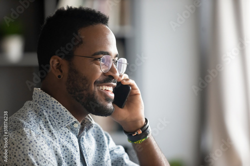 Fototapeta Smiling african business man making business call talking on phone obraz