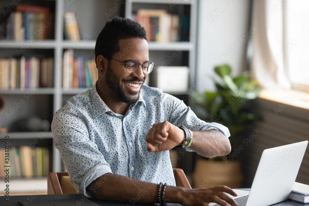 Fototapeta Happy african businessman worker looking at smart watch at work