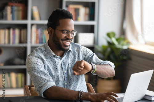 Obraz Happy african businessman worker looking at smart watch at work - fototapety do salonu