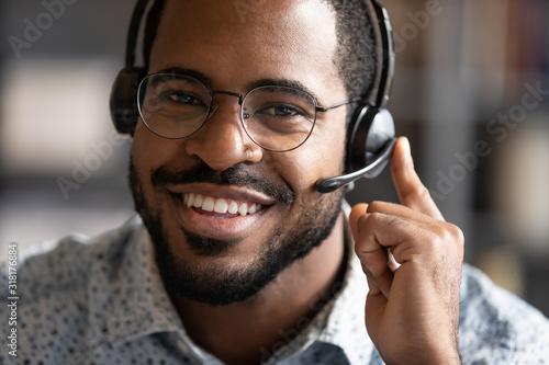 Happy friendly african telemarketing operator wear wireless headset portrait Fototapet