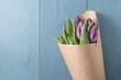canvas print picture - top view of purple tulips on blue wood background
