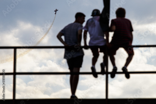 Teenagers watch the flight of the plane Canvas Print