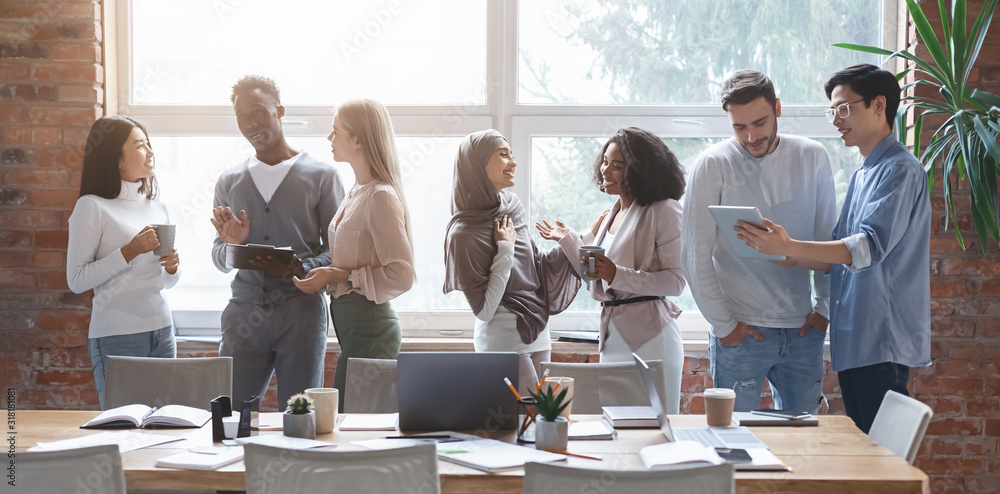 Fototapeta Multiracial young happy people sharing ideas while coffe break