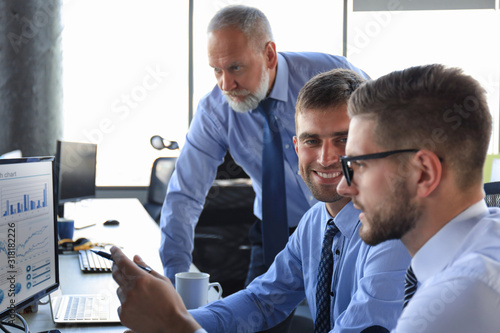 Fotografía Group of young business men in formalwear working using computers while sitting in the office