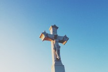 Low Angle View Of Jesus Christ On Cross Against Clear Sky