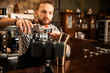 Young bartender filming vlog about his work