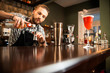 Professional bearded bartender is pouring alcoholic drink