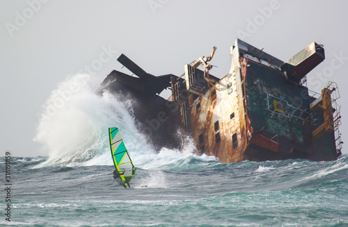 Foto Risky windsurfing in storm on the background of the abandoned ship wrack