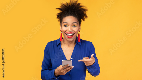 Amazed black woman pointing at mobile phone Wallpaper Mural
